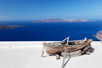 Old boat on the roof of the building on Santorini island, Greece