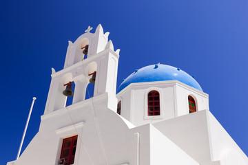 A white church with blue dome in Oia. Santorini island, Greece.