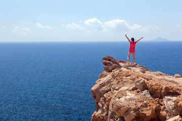 Happy woman on the rock with hands up. Winner, success, travel.