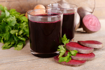 Glasses of fresh beet juice and vegetables on wooden background