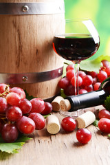 Wine with grapes on table on bright background