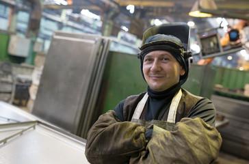 Caucasian welder worker at factory workshop background
