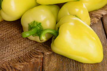 Yellow peppers on sackcloth on wooden table