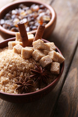 Brown sugar cubes and crystal sugar with spices in bowl