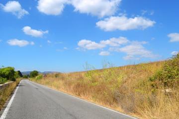 Strada asfaltata con cielo azzurro e nuvole