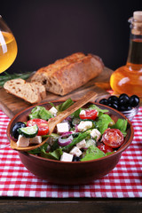 Bowl of Greek salad served with olive oil and glass of wine
