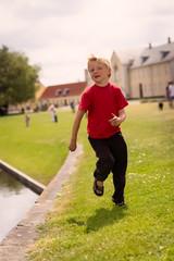 Boy running by water edge