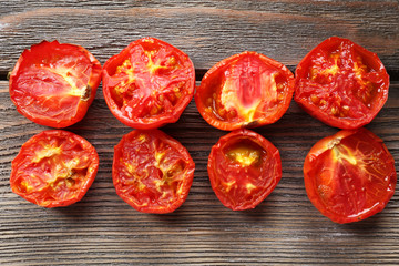 Delicious baked tomatoes on wooden background
