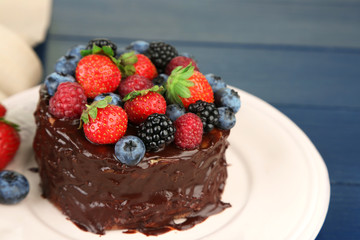 Tasty chocolate cake with different berries, on wooden table