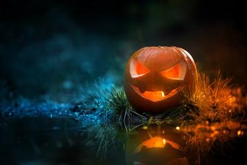 Creepy pumpkin next to a water stream