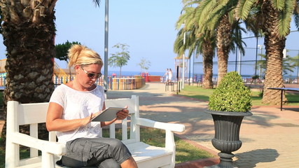 Woman sitting on a park bench and using digital tablet