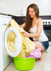Pretty young woman washing clothes in washer