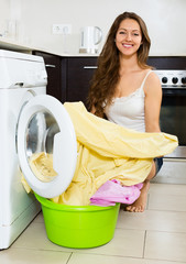 Pretty woman washing clothes in washer