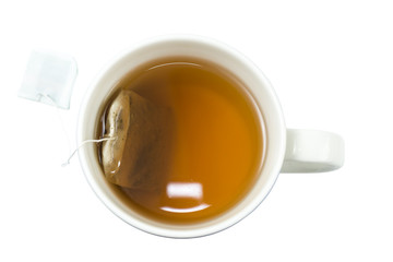 Closeup of a cup of tea and teabag viewed from above, isolated