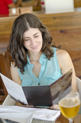 Woman reading restaurant menu card