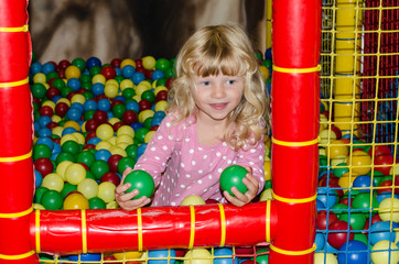 happy blond girl with colorful balls