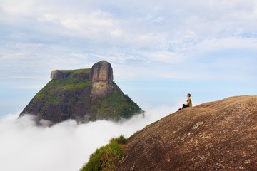 Woman sitting on edge of mountain Pedra Bonita, Rio de Janeiro,