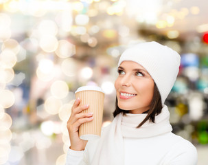 smiling young woman in winter clothes with cup