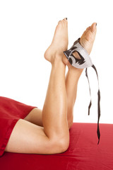 woman legs lay under sheet mask on foot