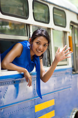 girl waving hand from the bus window