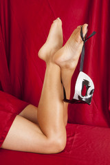 woman legs mask on foot red sheet