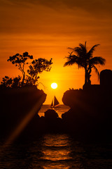 Sailboat at beautiful sunset above the tropical sea. Silhouette
