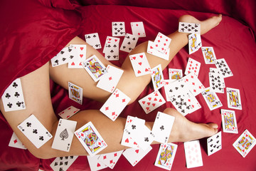 woman legs on sheet covered in cards