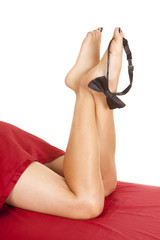 woman legs red sheet bow tie on toes