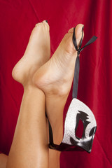 woman legs with mask hanging from toe red sheet