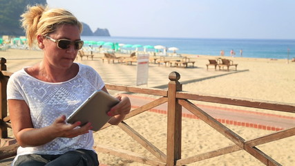 woman with tablet computer on the beach