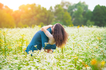 Young happy wedding couple hugging in the flower field