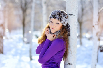 Outdoor winter portrait. Beautiful smiling girl posing in winter