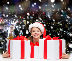smiling girl in santa helper hat with gift boxes