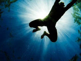 Man swimming in the sea with sunbeams shining