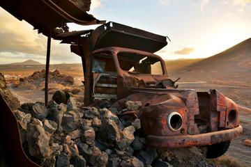 coche abandonado en el desierto al atardecer