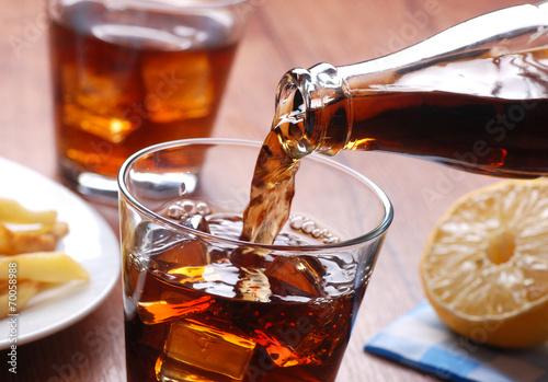 versare bevanda analcolica nel bicchiere di vetro - 70058988