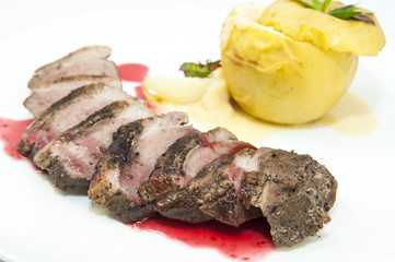 roast goose breast with apple sauce on white plate