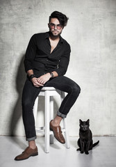 sexy fashion man model dressed casual posing with a cat