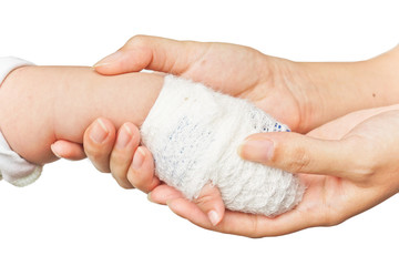 mother's hands holding baby's hand with bandage