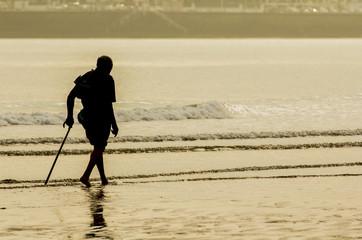 Anciano con bastón paseando por la playa
