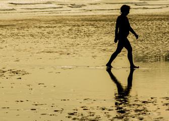 Mujer paseando por la orilla de la playa