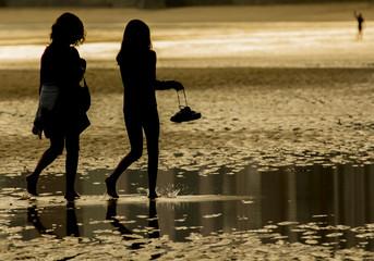 Madre e hija paseando por la playa