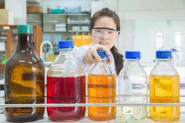 Asian scientist selecting bottle in shelf at laboratory (focus a