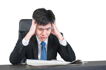 Worried Asian young businessman sitting with head in hands at of