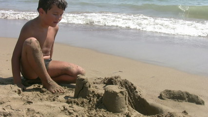 Child playing with sand on the beach