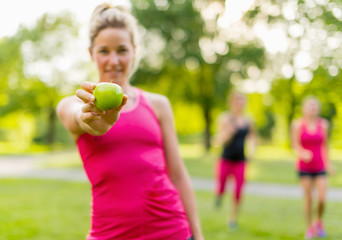 attractive blond woman eating an apple after a jog