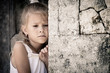 Portrait of sad little girl standing near stone wall