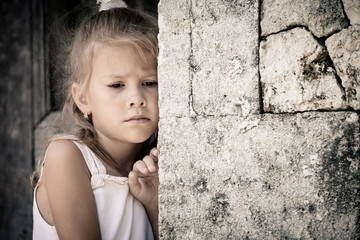 Portrait of sad little girl standing near stone wall