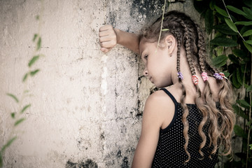 Portrait of sad little girl standing near stone wall in the day