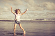 little girl  jumping on the beach at blue sea shore in summer va